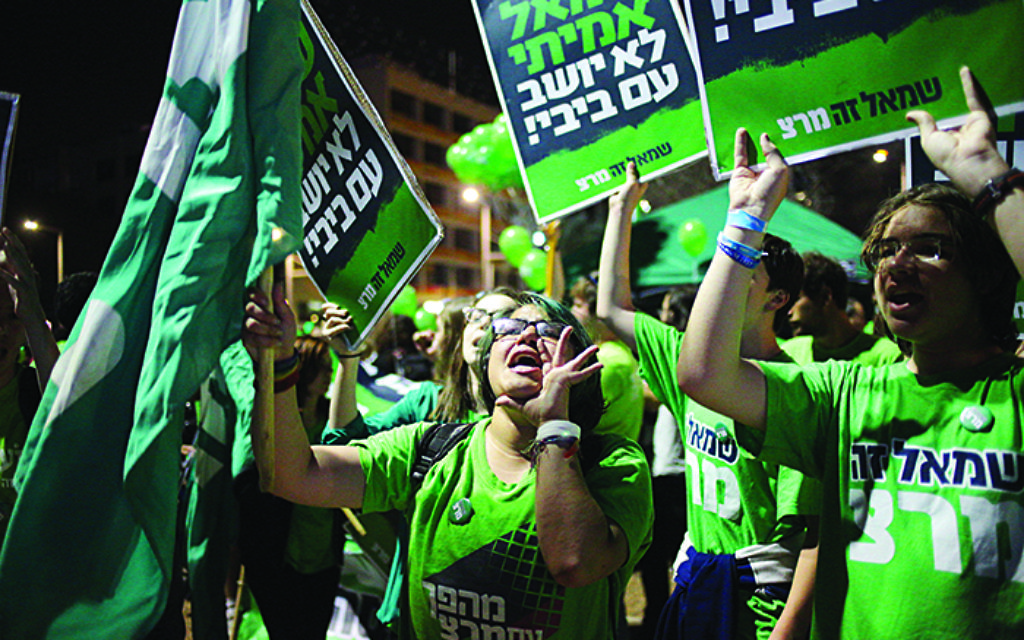 "Protesters hold banners in Hebrew that read, ""The real left does not sit with Bibi,"" during a rally against the government of Israeli Prime Minister Benjamin Netanyahu, in Tel Aviv, Saturday, March 7, 2015. Israel will hold legislative elections on March 17, 2015. (AP Photo/Ariel Schalit)"