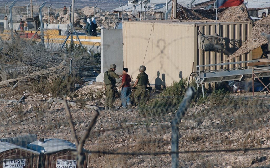 Israeli soldiers at Kalandia checkpoint in occupied West Bank taking Palestinian minors out of sight behind a building and assaulting them (presumably in an effort to obtain information from them). Other soldiers interrupted my photo-taking as the pictured soldiers repeatedly struck the kid in the head.