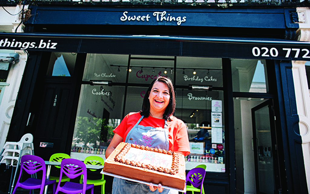 Natalie Allen holds up a cake outside her Primrose Hill boutique cafe
