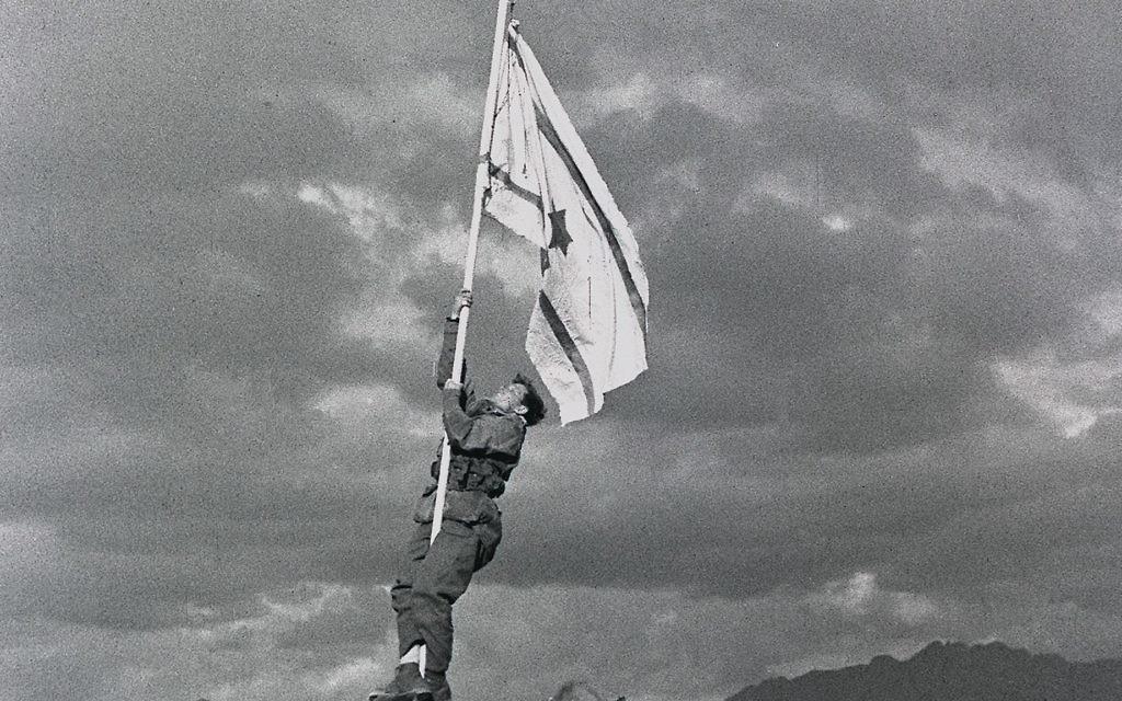 "Captain Avraham ""Bren"" Adan raising the Ink Flag at Umm Rashrash (a site now in Eilat), marking the end of the war."