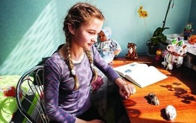Valentina's daughter, Yulia, 11, one of many internally displaced people in a temporary shelter. Yulia, pictured with her pets, wants to be a police officer