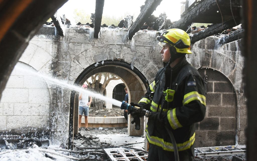 A firefighter continues to put out the blaze after a fire heavily damages the Church of Loaves and Fishes on Sea of Galilee   (Photo by Avihu Sahpira/Israel Sun)