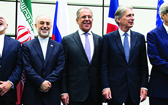 From left to right: European Union High Representative Federica Mogherini, Iranian Foreign Minister Mohammad Javad Zarif, Head of the Iranian Atomic Energy Organization Ali Akbar Salehi, Russian Foreign Minister Sergey Lavrov, British Foreign Secretary Philip Hammond and US Secretary of State John Kerry pose for a group picture at the United Nations building in Vienna, Austria, Tuesday, July 14, 2015. . (Joe Klamar/Pool Photo via AP)