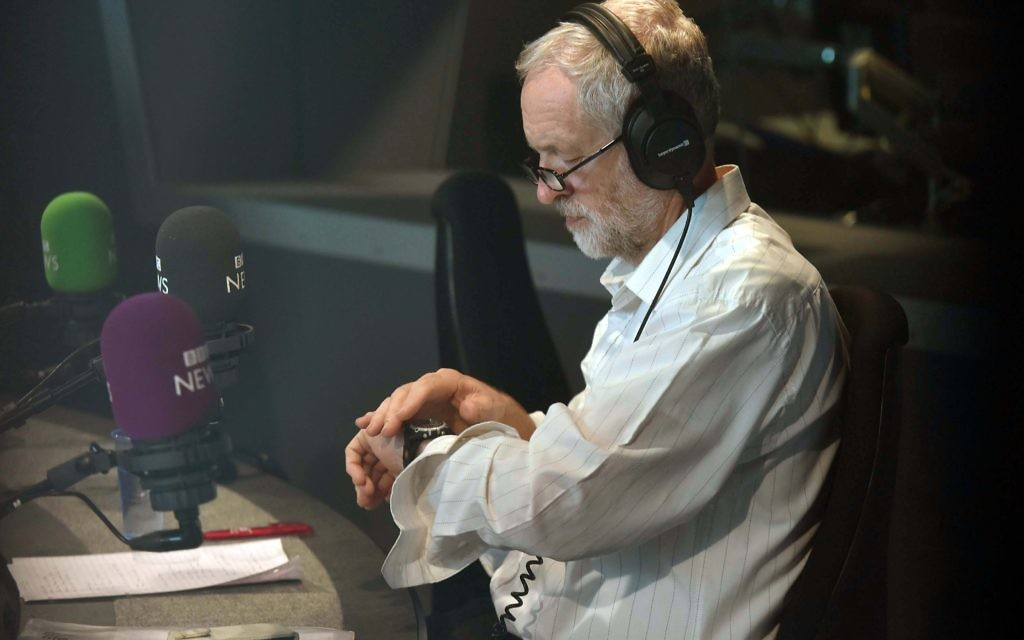 "For use in UK, Ireland or Benelux countries only   Undated BBC handout photo of Labour leadership contender Jeremy Corbyn looking at his watch during a call-in with listeners on BBC Radio 4's World At One programme, where he hit back at ""disgusting"" claims that he is anti-Semitic and denied he has links with a controversial Lebanese activist. PRESS ASSOCIATION Photo. Issue date: Wednesday August 19, 2015. The left-winger's campaign to take the party's job has been surrounded in controversy over his dealings with extremists and suggestions that some of his supporters are peddling abuse against Jews on social media. See PA story POLITICS Labour. Photo credit should read: Jeff Overs/BBC/PA Wire  NOTE TO EDITORS: Not for use more than 21 days after issue. You may use this picture without charge only for the purpose of publicising or reporting on current BBC programming, personnel or other BBC output or activity within 21 days of issue. Any use after that time MUST be cleared through BBC Picture Publicity. Please credit the image to the BBC and any named photographer or independent programme maker, as described in the caption."