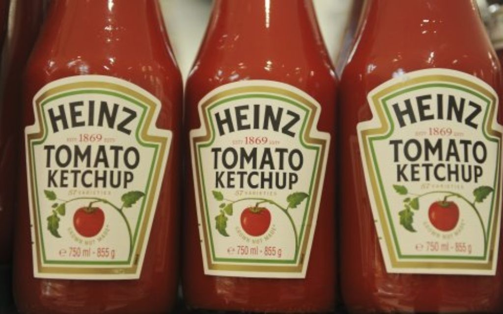 Bottles of Heinz ketchup on display in a supermarket.