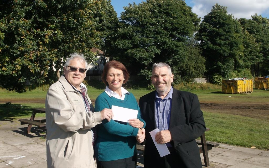 `Heather Fletcher is receiving the donation from Harvey Hurwitch, while Frank Shatliff, Chairman of the Prestwich Carnival Committee is standing on Heather's left.