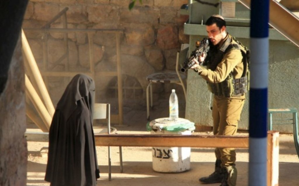 An Israeli soldier aims his rifle at an 18-year-old Palestinian student.