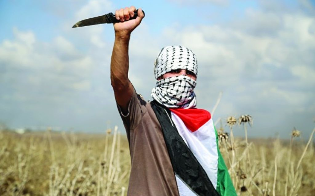 A Palestinian protester, holding a knife, looks on during clashes with Israeli security forces near the border fence between Israel and the Gaza Strip