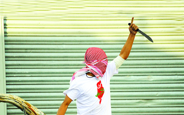 A Palestinian demonstrator raises a knife, during clashes with Israeli police, in Shuafat refugee camp in Jerusalem,, Oct. 2015.  (AP Photo/Mahmoud Illean)