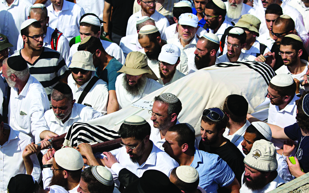 """Israeli relatives and friends carry the body of Rabbi Nehemia Lavi, during his funeral at a cemetery in Jerusalem, Sunday, Oct. 4, 2015. In an unprecedented measure, Israeli police barred Palestinians from Jerusalem's Old City on Sunday in response to stabbing attacks that killed two Israelis and wounded three others, as Israel's prime minister vowed a """"harsh offensive"""" to counter rising violence. (AP Photo/Sebastian Scheiner)"""