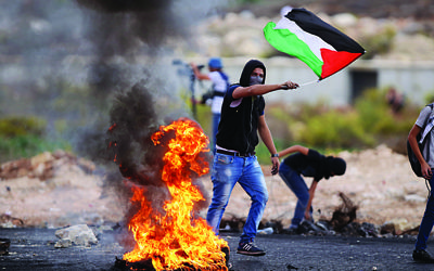 Image #: 40199080    (151018) -- RAMALLAH, Oct. 18, 2015 (Xinhua) -- A Palestinian protester holds national flag during clashes with Israeli soldiers, in Beit El, on the outskirts of the West Bank city of Ramallah, on Oct. 18, 2015.