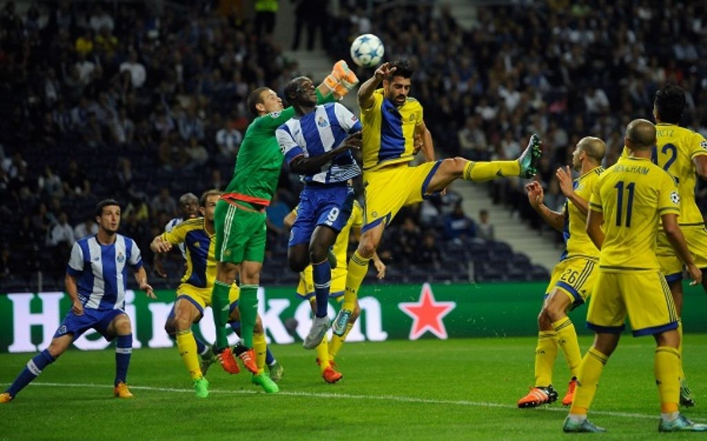 Porto's Vincent Aboubakar, center, jumps for the ball with Maccabi's goalkeeper Predrag Rajkovic, center left, and Omri Ben Harush during the Champions League group G soccer match between FC Porto and Maccabi Tel-Aviv FC at the Dragao stadium in Porto, Portugal, Tuesday, Oct. 20, 2015. (AP Photo/Paulo Duarte)