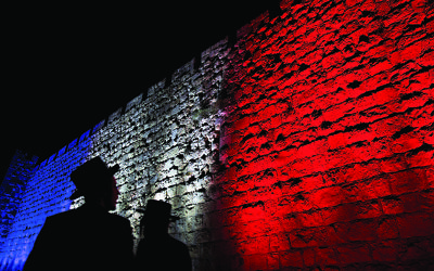 Two Orthodox Jews look at Jerusalem's Old City walls illuminated by the colours of the French national flag in solidarity with France after attacks in Paris, in Jerusalem, Sunday, Nov. 15, 2015. (AP Photo/Ariel Schalit)