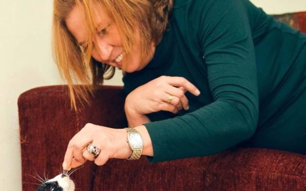 """Tzipi Livni posted a picture on her Facebook page of her playing with a black and white cat. """"No way will I get a foreign passport for little one,"""" she wrote."""
