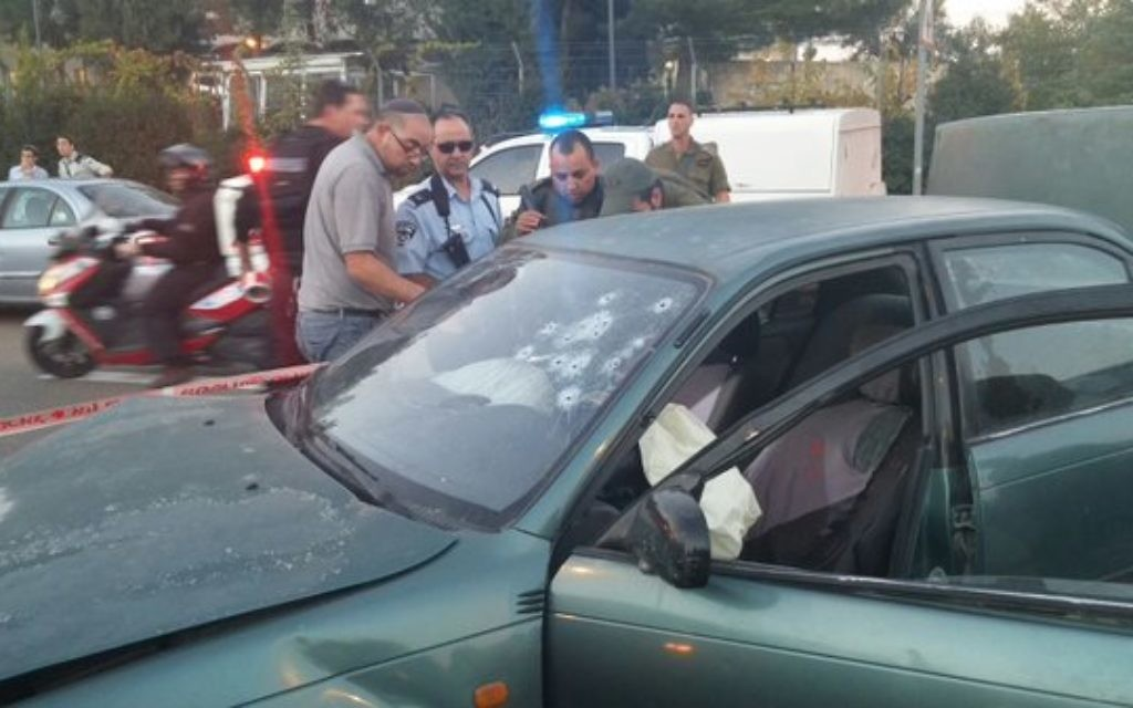 Bullet holes in a car are examined following the attack (Image via Israel News Flash on Twitter)