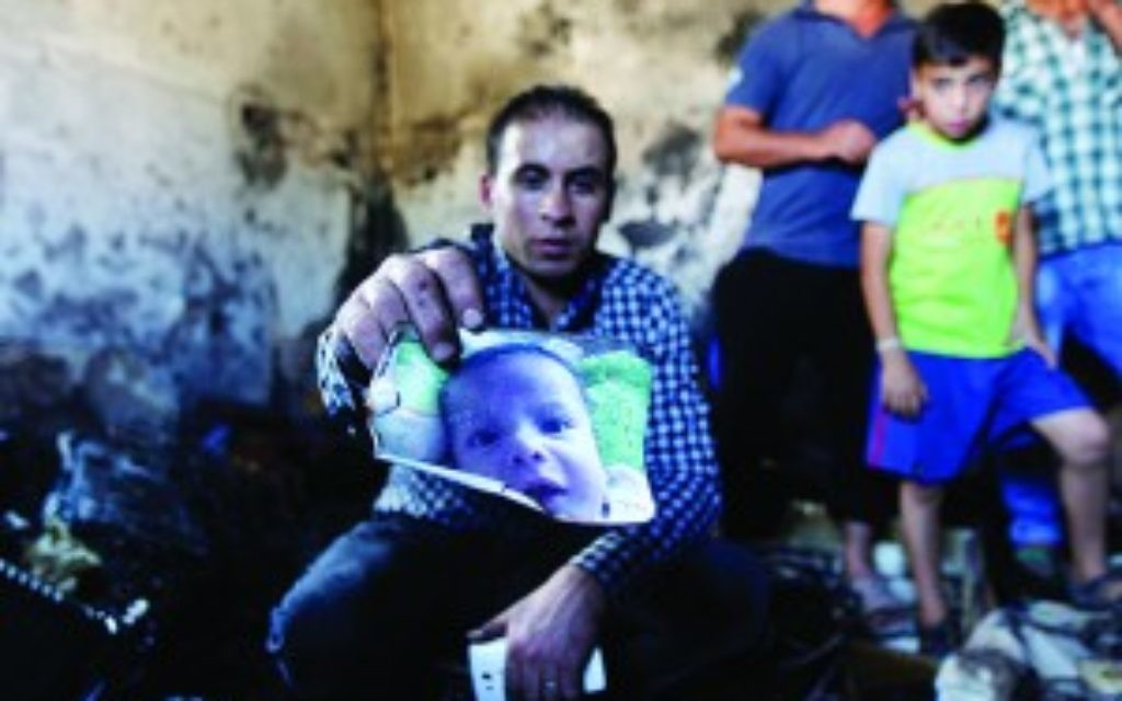 A relative holds up a photo of a one-and-a-half year old boy, Ali Dawabsheh, in a house that had been torched in a suspected attack by Jewish settlers in Duma village near the West Bank city of Nablus, Friday, July 31, 2015