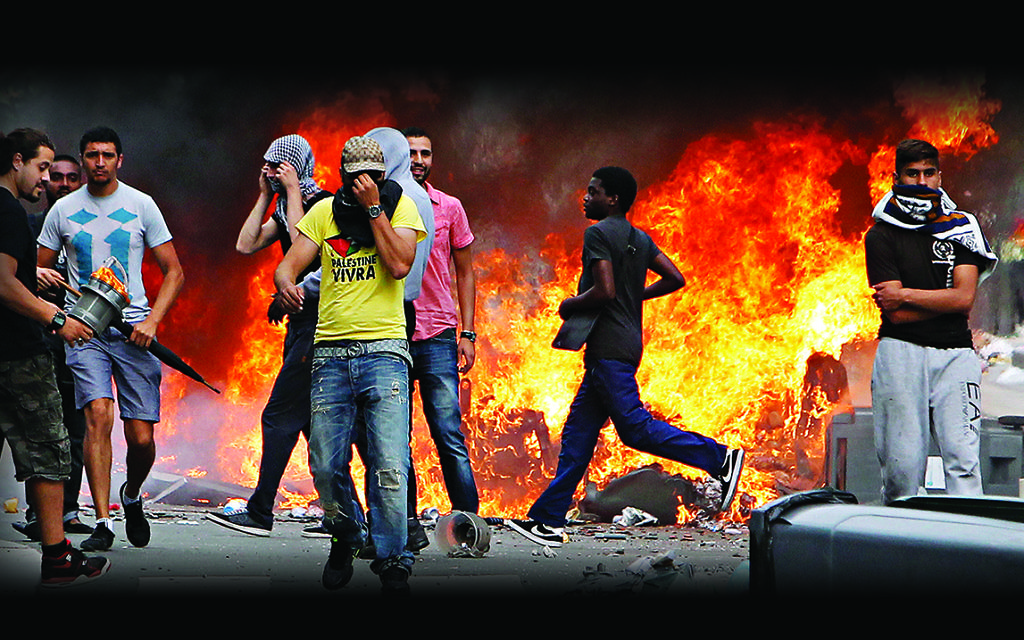 Rioters face riot police, following a pro-Palestinian demonstration, in Sarcelles, north of Paris, Sunday, July 20, 2014. French youth defying a ban on a protest against Israel's Gaza offensive went on a rampage in a Paris suburb, setting fire to cars and garbage cans after a peaceful demonstration. (AP Photo/Thibault Camus)
