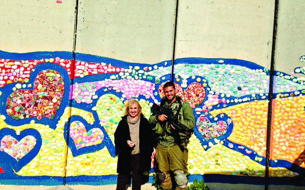 Gillian with a soldier and part of Path to Peace mosaic