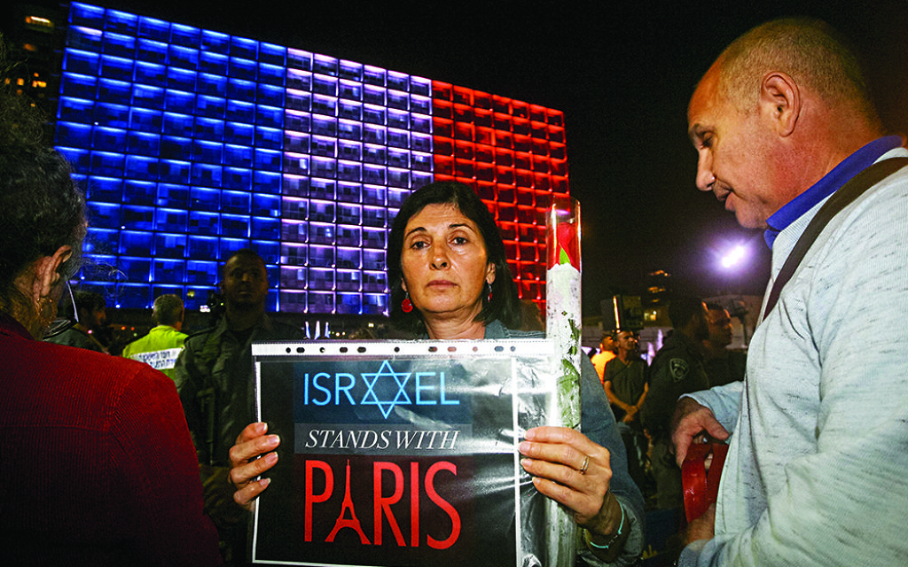 """Photo by Roni Shutzer/Israel Sun 14-11-2015 FREELANCE PHOTOGRAPHER SPECIAL %%% APPLY  Approximately 2,500 Israelis gathered in Tel Aviv's Rabin Square on Saturday evening to express solidarity with the people of France following a massive terror attack in Paris that left 129 people dead and 352 wounded. Representing Israel's governing coalition at the rally, Interior Minister Silvan Shalom told the  French Ambassador to Israel Patrick Maisonnave and other assembled dignitaries that """"Israel stands by you and we will help you. We will defeat those who want to destroy our values."""" """"We send our condolences to the French president, government and the entire French people. We will stand shoulder to shoulder with you as a nation that understands better than others what it is to be under a terror assault.""""  Israel's frail former president Shimon Peres also addressed the crowd, as did Israel's opposition leader Isaac Herzog and French ambassador Patrick Maisonnave. All the speakers emphasized Israel and France's common dedication to freedom and democratic values, and the phrase """"vive la liberté"""" rang out repeatedly. The gathering concluded with the singing of the French and Israeli national anthems, with many in the crowd singing along.    עצרת הזדהות עם קורבנות פיגועי הטרור בצרפת התקיימה הערב (שבת) בכיכר רבין. בניין עיריית תל אביב-יפו הואר בצבעי דגל הרפובליקה הצרפתית כאות הזדהות עם קורבנות הפיגוע וכסולידריות עם צרפת. נשיא המדינה לשעבר שמעון פרס אמר בעצרת: """"אחינו הצרפתים, ביום קשה זה אנו אחים לאבלכם הכבד. מלחמתכם - מלחמתנו""""."""
