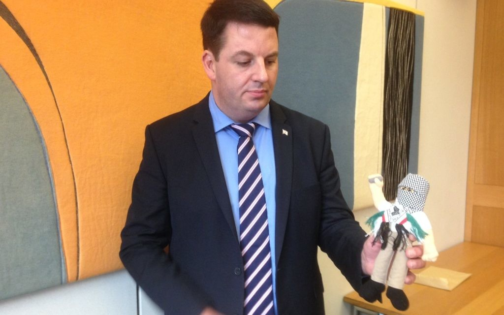 """MP Andrew Percy, brandishing one of 4,000 """"terror dolls"""" seized by Israeli authorities in December."""