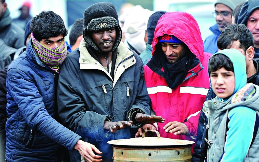 "Migrants warm their hands at ""the Jungle"" camp in Calais"
