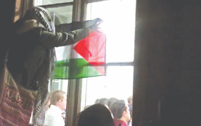 An anti-Israel protester waves a Palestinian flag through the window of the event at KLC with an Israeli speaker