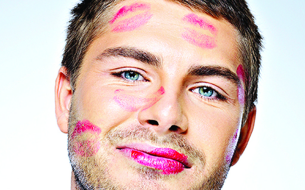 man with face full of lipstick marks of kisses