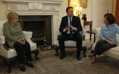 Britain's Prime Minister David Cameron, center, gestures as he talks to a group of Holocaust survivors, including Susie Lind, inside Downing Street to mark Holocaust Memorial Day, with TV presenter Natasha Kaplinsky, right, in London, Wednesday, Jan. 27, 2016. (AP Photo/Alastair Grant, Pool)