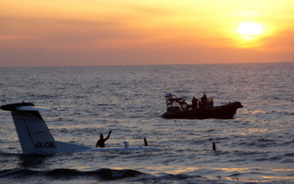 Police boats are seen next to a private plane that crash landed in the Mediterranean Sea, in Tel Aviv, Israel, Sunday, April 3, 2016. Initial reports said the pilots were not seriously injured. (AP Photo/Sebastian Scheiner)