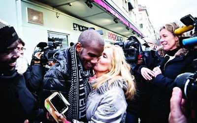 Lassana Bathily is embraced by a well-wisher outside the Hyper Cacher on the first anniversary of the attack