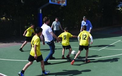 Volunteers, mad the occasional ambassador, join in the soccer kickabout