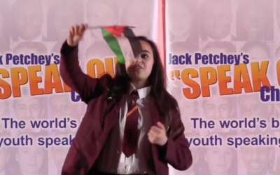 Leanne Mohamad waving a Palestinian flag at the end of her speech