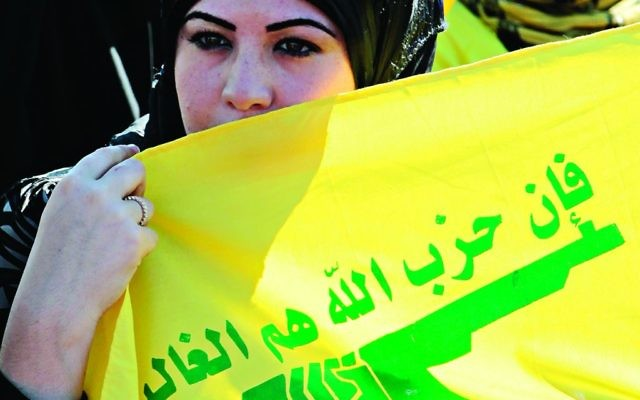 A woman holding a Hezbollah flag during an Al Quds Day march