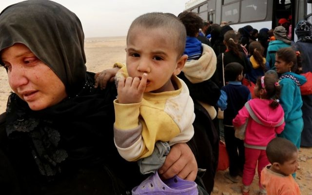 Syrian refugees wait in line to get on a bus after crossing into Jordan at the Hadalat reception area on the Syrian-Jordanian border.