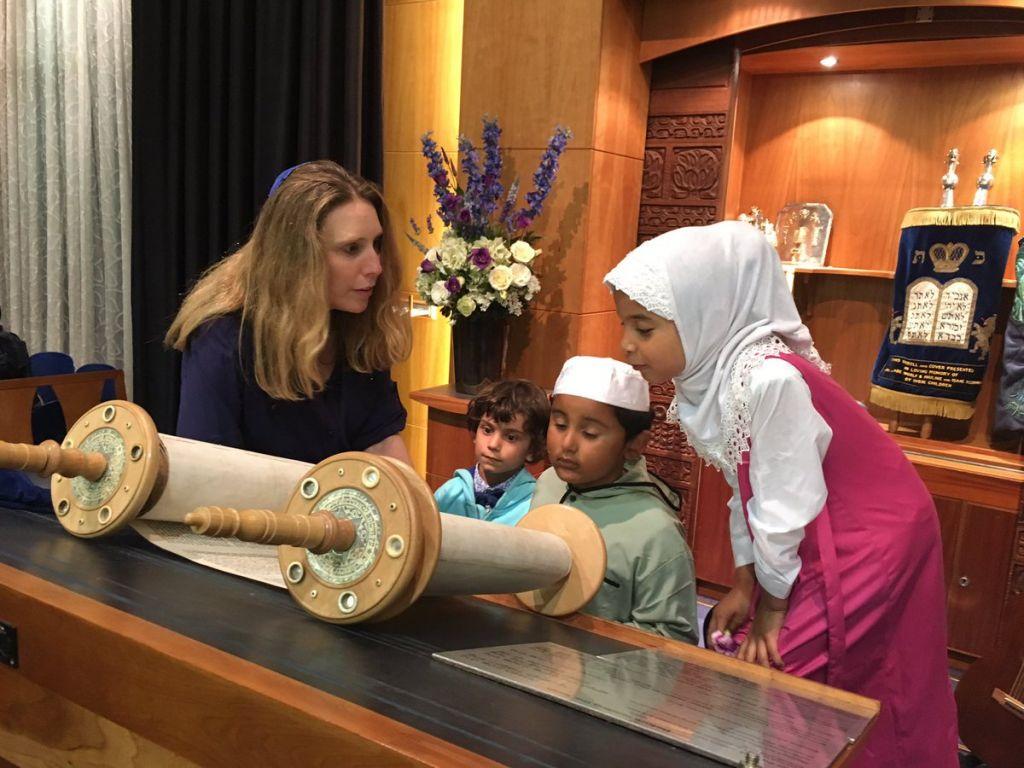 Rabbi Miriam Berger shows Muslim children a Torah scroll