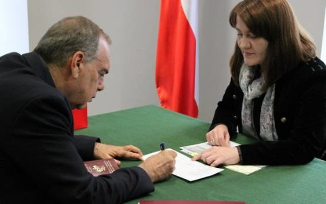Avram Grant singing official documents to accept his passport (Picture credit: Konrad Jagodzinski / Polish Embassy UK)