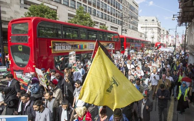 A Hezbollah supporter waves the terror flag in central London during Al Quds Day.