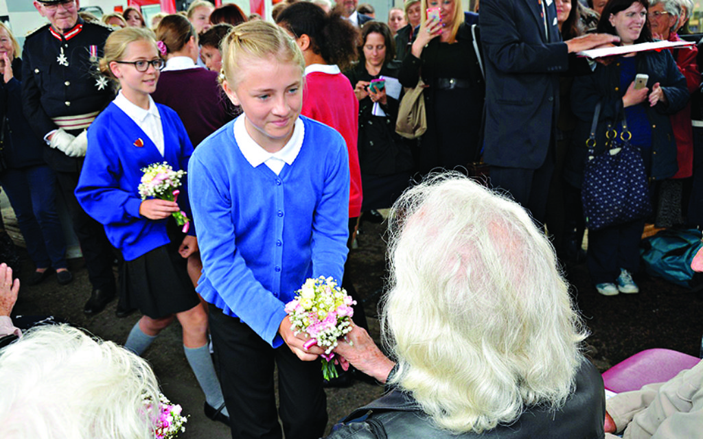 A girl hands a posy to a 'Kind'.