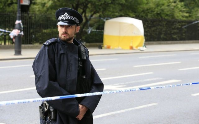 A police officer stands guard near a tent in Russell Square, after a knife attack in which a woman in her 60s was killed and five people were injured. A 19-year-old man has been arrested  (Photo credit: Jonathan Brady/PA Wire.)