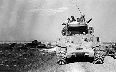 A Israeli tanks passes the remains of a Syrian tank in the Golan Heights in Israel during the Yom Kippur War on Oct. 9, 1973. (AP Photo/Spartaco Bodini)