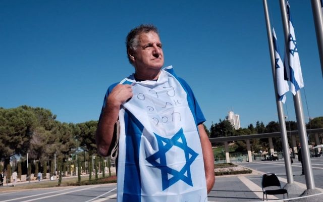A mourner, draped in the Israeli flag, pays his own personal tribute to Peres