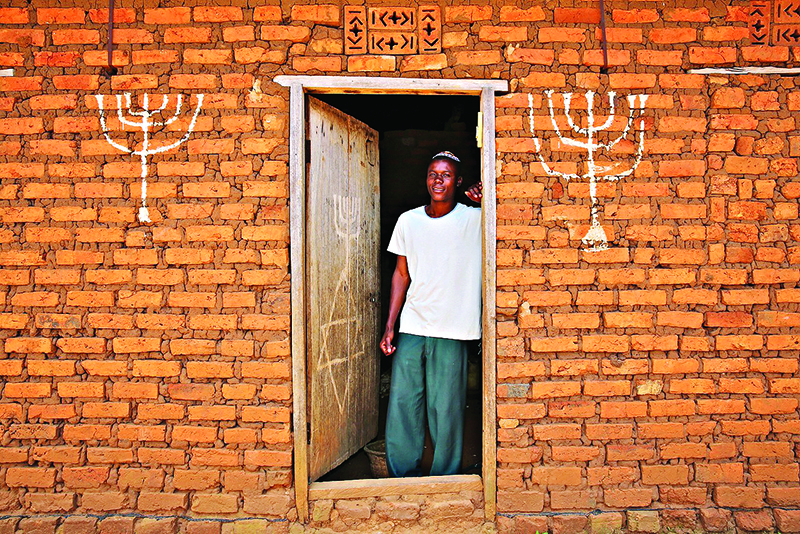 Joseph Mwanika in the doorway of a house in Nalubembe village in kikubu district Uganda