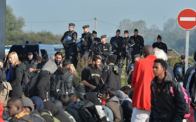 Police create a cordon as several large fires broke out in the near deserted migrant camp in Calais, northern France on the third day of the operation to clear the Jungle. (Photo credit: John Stillwell/PA Wire)