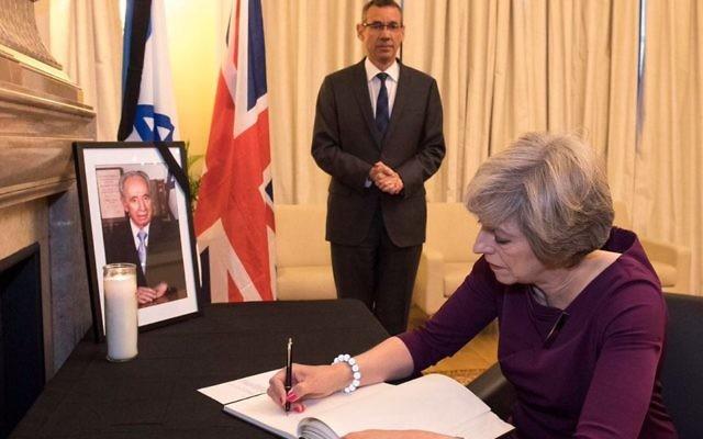 Theresa May signing the book of condolences at the Israeli Embassy in London