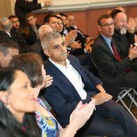 Sadiq Khan (centre) listening to a speaker