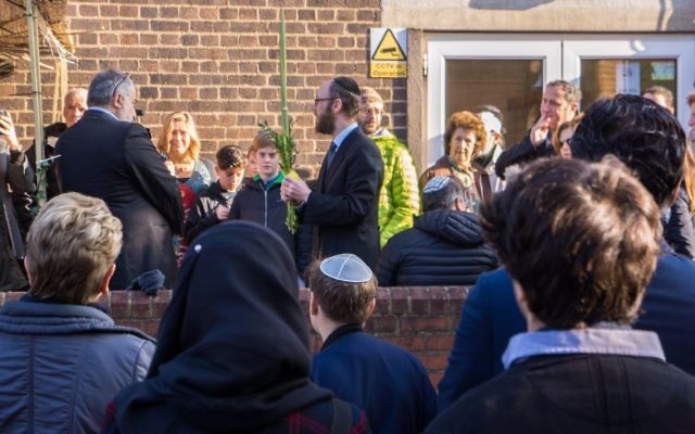 Rabbi Baruch Levine outside the mosque waving the lulav and etrog