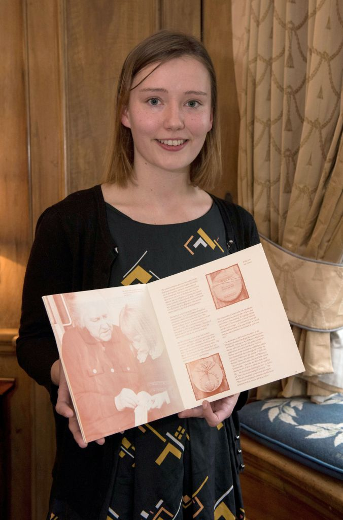 Caitriona Topping with book on Jane Haining in which she is pictured as a four year old with Agnes O'Brien and Jane Haining's medal. (Photo credit: Andrew O'Brien/Church of Scotland/PA)