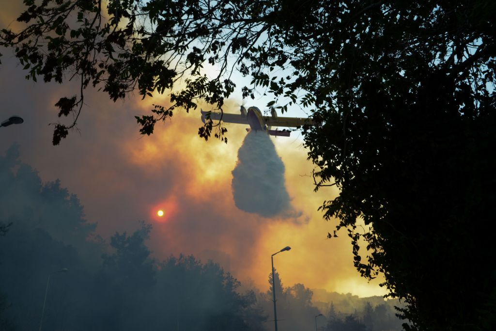 An Israeli firefighter helps extinguish a fire in the northern Israeli port city of Haifa on November 24, 2016. Hundreds of Israelis fled their homes on the outskirts of the country's third city Haifa with others trapped inside as firefighters struggled to control raging bushfires, officials said. Phtoo by: Moran Mayan - JINIPIX