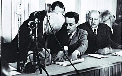 David Ben Gurion (left) signing the Declaration of Independence held by Moshe Sharet, with Eliezer