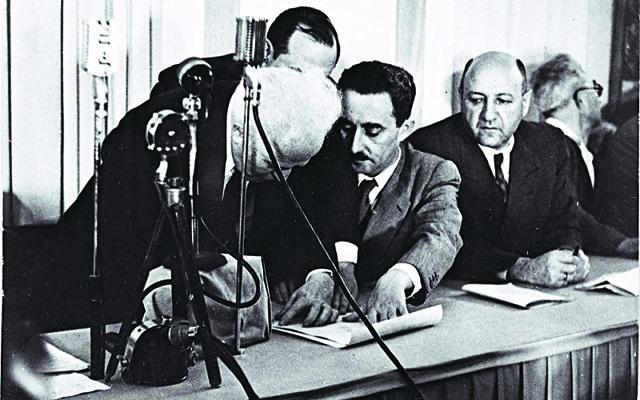 David Ben Gurion (left) signing the Declaration of Independence held by Moshe Sharet, with Eliezer